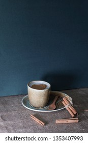 White cup of salep milky hot drink of Turkey with cinnamon powder healthy spice on black wooden background