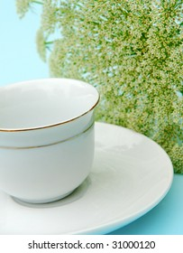 white cup and saucer with fresh flower in background