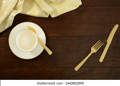 White cup and saucer, gold plastic cutlery and napkin on dark wooden background.  Flat lay composition with room for text