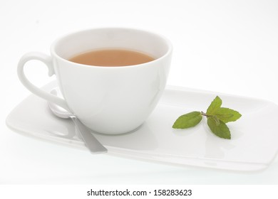 a white cup and saucer with herbal tea and a sprig of mint