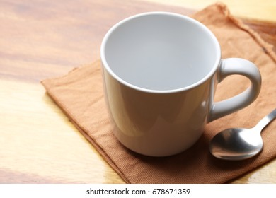 white cup and spoon on wood floor