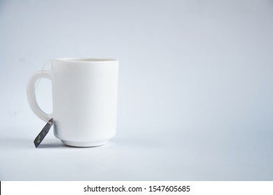 A white cup with a tea bag is standing on the table. On white background