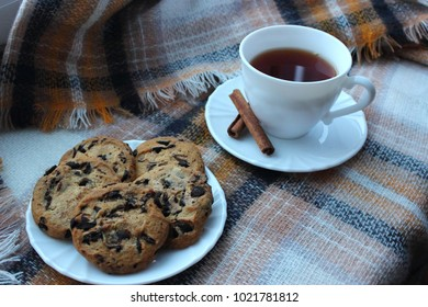 A white cup of tea with cinnamon sticks and homemade chocolate chip cookies. Perfect for breakfast or snack on cold winter day.