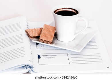 white cup of tea with green notebook and wafers
