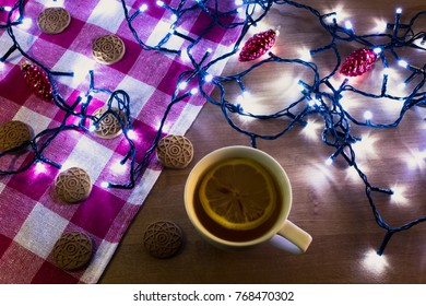 White cup of tea with lemon surrounded by Christmas (fairy) lights, gingerbread cookies and red Christmas decorations on a wooden table with a red and white napkin