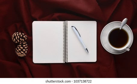 White cup with tea, notebook and pen, pine cones on a red sheet. Winter morning tea drinking. Top view. Flat lay. Minimalism trend.
