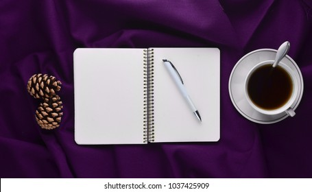 White cup with tea, notebook and pen, pine cones on a violet sheet. Winter morning tea drinking. Top view. Flat lay. Minimalism trend.