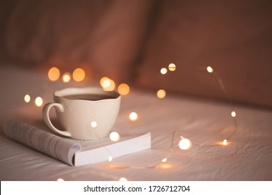White cup of tea staying on open book with glowing Christmas lights at background. Good morning. Breakfast. Stay at home.