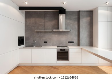 White cupboard with built in household appliance, electric stove, oven, sink on worktop, wooden laminate on floor and extractor hood on grey wall. House with modern interior at contemporary kitchen