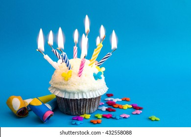 white cupcake with candles and decoration on blue background