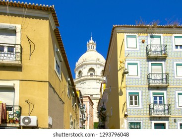 White cupola of the National Pantheon seen behind two beautiful colorful buildings in Alfama, Lisbon, Portugal