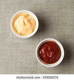 white cups with ketchup and cheese on gray napkin made from canvas