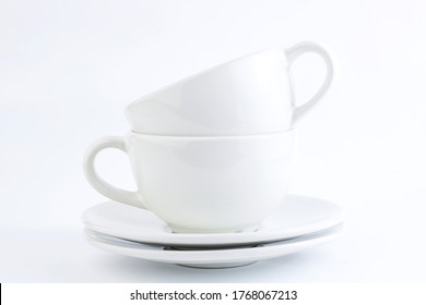White cups and saucers stacked on a white background. Copy spaceite cups and saucers stacked on a white background. Copy space