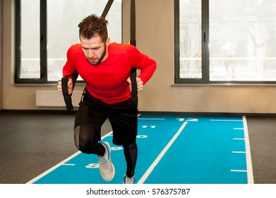 white curly bearded sporty man exercising with trx  fitness straps in gym