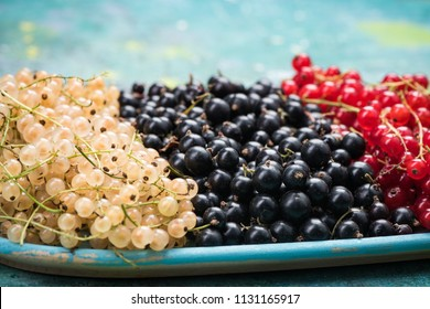 White currant, redcurrant and blackcurrant, on wooden plate.