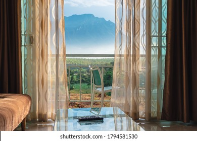 White curtain by the window and view of the mountain with light from the sunset, Beautiful curtain make the house more livable,The atmosphere of relaxation at living room in a holiday close to nature.