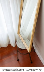 The white curtain reflected in the mirror on the iron chair