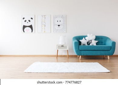 White cushions on aquamarine sofa next to cabinet and rug in kid's room with posters