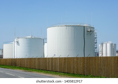 white cylindrical storage tanks for petroleum products against a blue sky