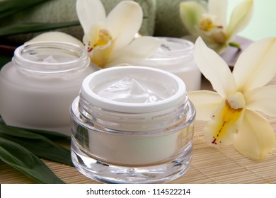 White Cymbidium orchid flower and jar of moisturizing face cream for spa treatment.