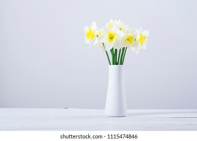 white daffodils at china vase on bright wood table