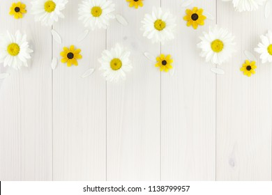 White daisies and garden flowers on a white wooden table. The flowers are arranged in the upper part, the empty space left below.
