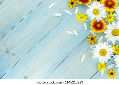 White daisies and garden flowers on a light blue worn wooden table. The flowers are arranged in the upper corner, the empty space left below.