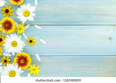 White daisies and garden flowers on a light blue worn wooden table. Empty space on the other side.