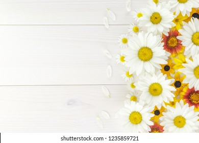 White daisies and garden flowers on a white wooden table. The flowers are arranged side, empty space left on the other side.