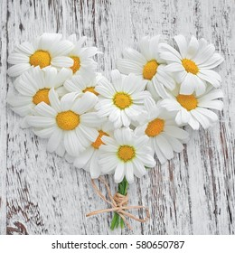White daisies in the shape of a heart on the old wooden background.