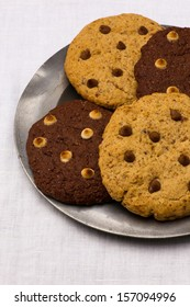 White and dark chocolate chip cookies on tin plate, white canvas