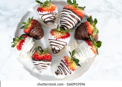White and dark chocolate dipped strawberries on a white cake stand.