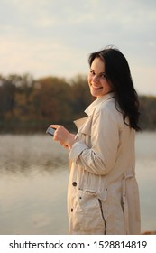 White dark haired girl looks at the cellphone and swipes a finger on the phone screen on a background of an autumn lake