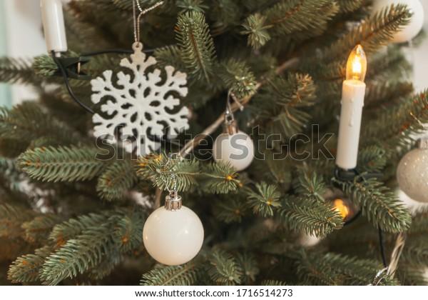 White decoration balls snowflakes on the Christmas tree close-up. Stylish white monochrome Christmas tree decoration background texture. Fake artificial Christmas tree