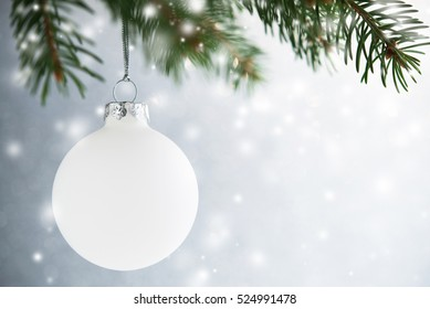 White decorative ball on the christmas tree on glitter bokeh background with blurred snow. Merry christmas card. Winter xmas theme. Happy New Year. Snowing.