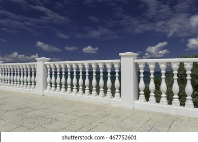 White decorative fence on the waterfront of the Anapa city resort on the Black Sea coast. Blue cloudy sky, water with an emerald hue.