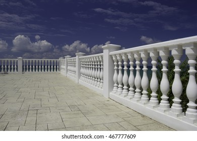 White decorative fence on the waterfront of a resort on the Black Sea coast. Blue cloudy sky, water with an emerald hue, green tree leaves. Selective Focus on foreground.