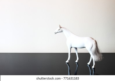 White decorative pony equine horse toy on black shiny background and white wall
