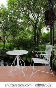 White decorative wrought iron garden chair and table in a tropical garden with trees and a pond.