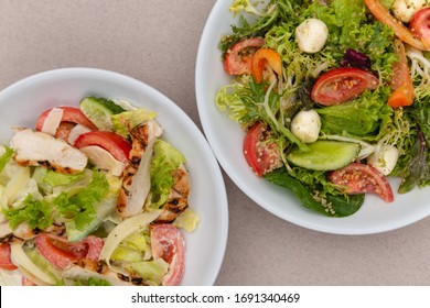 white deep plates with fresh salad ingredients mixed with sauce placed on an attractive background. A place for a menu, banner or advertisement