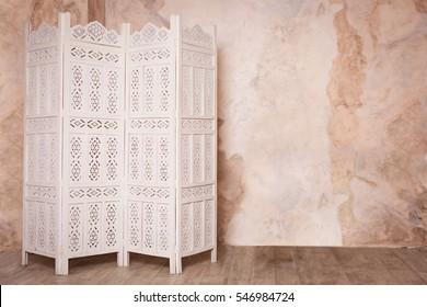 White delicate decorative wood panel on brown plaster wall. Boudoir wedding room. Retro folding screen. Vintage ornate carved folding screen.
