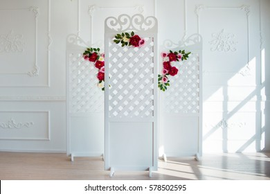 White delicate decorative wood panel in classical interior. Boudoir wedding room. Retro folding screen with flowers. Vintage ornate carved folding screen.