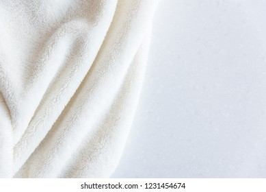 White delicate soft background of plush fabric folds on white background. Copy space. Flat lay.
