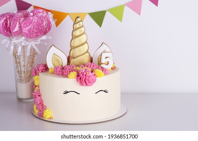 white delicate unicorn cake with pink lollipops on a white background. birthday cake