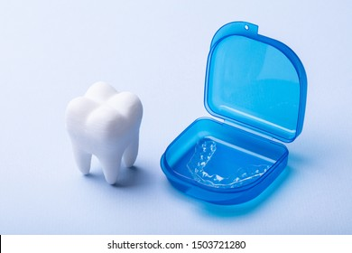 White Dental Model And Transparent Mouth Guard In Case Over Blue Surface