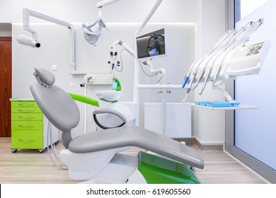White dental office with grey chair, modern microscope and led lamp