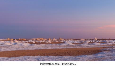 White desert in Egypt, Farafra, wind eroded rock formations at sunset of pink light.
