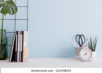 White desk, blue wall mock up, box, succulent plant, clock, pencils and brushes.