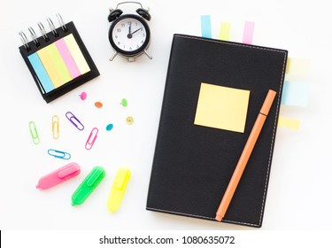 White desk with a clock, modern black notepads, stickers, color markers and clips. Blank notebook page for input the text. White background, flat lay style.
