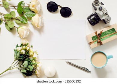 White desk with coffee cup, sunglasses, roses and film camera. Empty sheet in the middle. Top view, flat lay, copyspace.